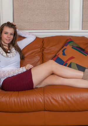Wild haired brunette Zoey Lee on the couch showing her shaved quim