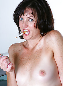 Hot brunette MILF Sydney lights up a cigarette and shows pussy