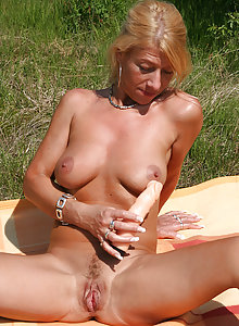 Mature Sylvie outside playing with her lifelike rubber toy