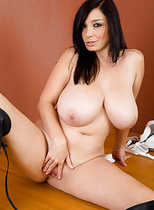 Dark haired and very busty Michelle B posing elegantly on a table