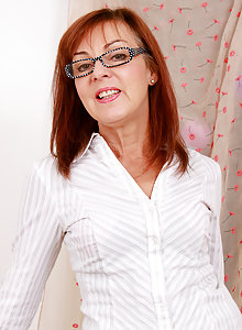 Sexy older secretary Georgie takes off her glasses and whips down her knickers to show her hot pussy