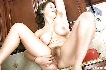 Kinky Celia mounts her curvy ass on the kitchen bench and rubs her meaty pink hairy bush until it makes her moan softly.
