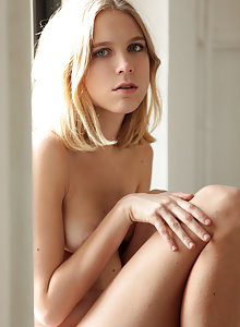 Slim blonde Nora Pace waits by the window as she gets nude in her high heels