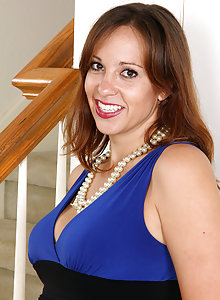 Elegant brunette MILF Cassandra Johnson strips down to her pearls and stockings to rub her pussy