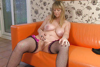 Hairy woman Sophie UK is ready for a little solo play, but she wants to watch herself as she strips out of her pink nightie into nothing but her black fishnets while rubbing her hairy pussy.