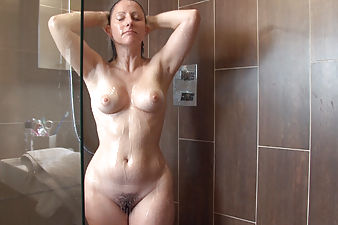 Amber Lustful washes her hairy pussy in the shower