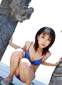 Lovely Japanese model smiles as she poses in her bikini on the beach