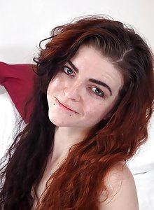 Pale skinned redhead Scarlet Contemptress frolicks on the bed and bends over to show her hairy crack