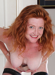 Redheaded and 48 year old Tami Estelle strips nake and spreads wide