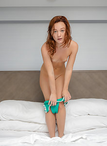 Petite redhead Sara Barnard gets nude on the bed showing her tiny tits