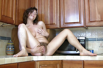 Luca on the kitchen counter fingering hairy pussy