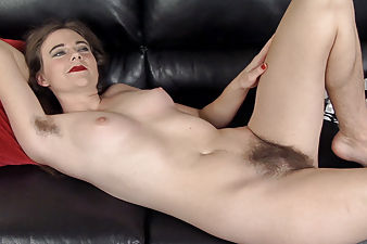 Camille masturbates on black leather sofa