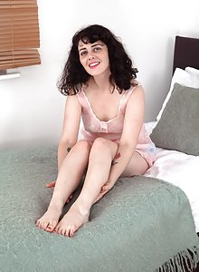 Hairy brunette girl Dion takes off her pink dress to unwind in bed