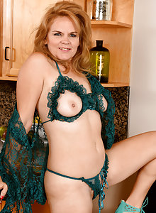 Redhead mature lady Micky Lynn takes off her panties and bra to play with her big lips
